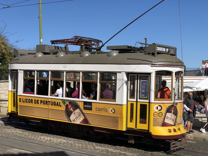 Street tram in Lisbon, Portugal Lisbon Portugal Transportation Mode Of Transportation Public Transportation Track Sky Railroad Track Rail Transportation Day Cable Car Land Vehicle Nature City Real People Architecture Group Of People Large Group Of People Building Exterior Yellow Men