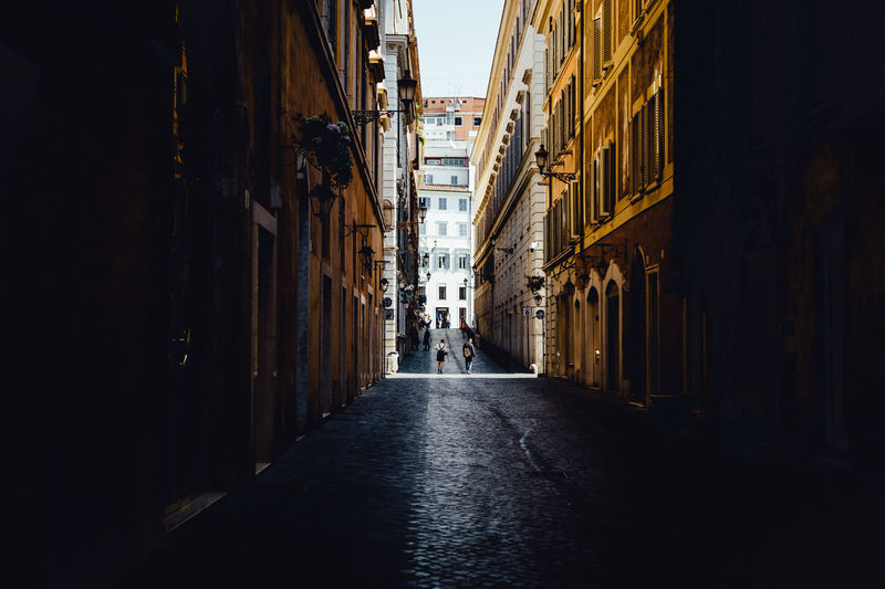 City Life Moving Around Rome Rome Stories From The City Alley Architecture Building Exterior Built Structure City Cobblestone Lifestyles Light And Shadow Narrow Street Old Buildings Real People Street Streetphotography vanishing point Walking