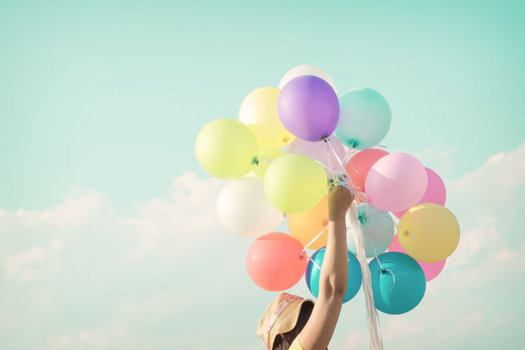 Low angle view of woman holding balloons against sky