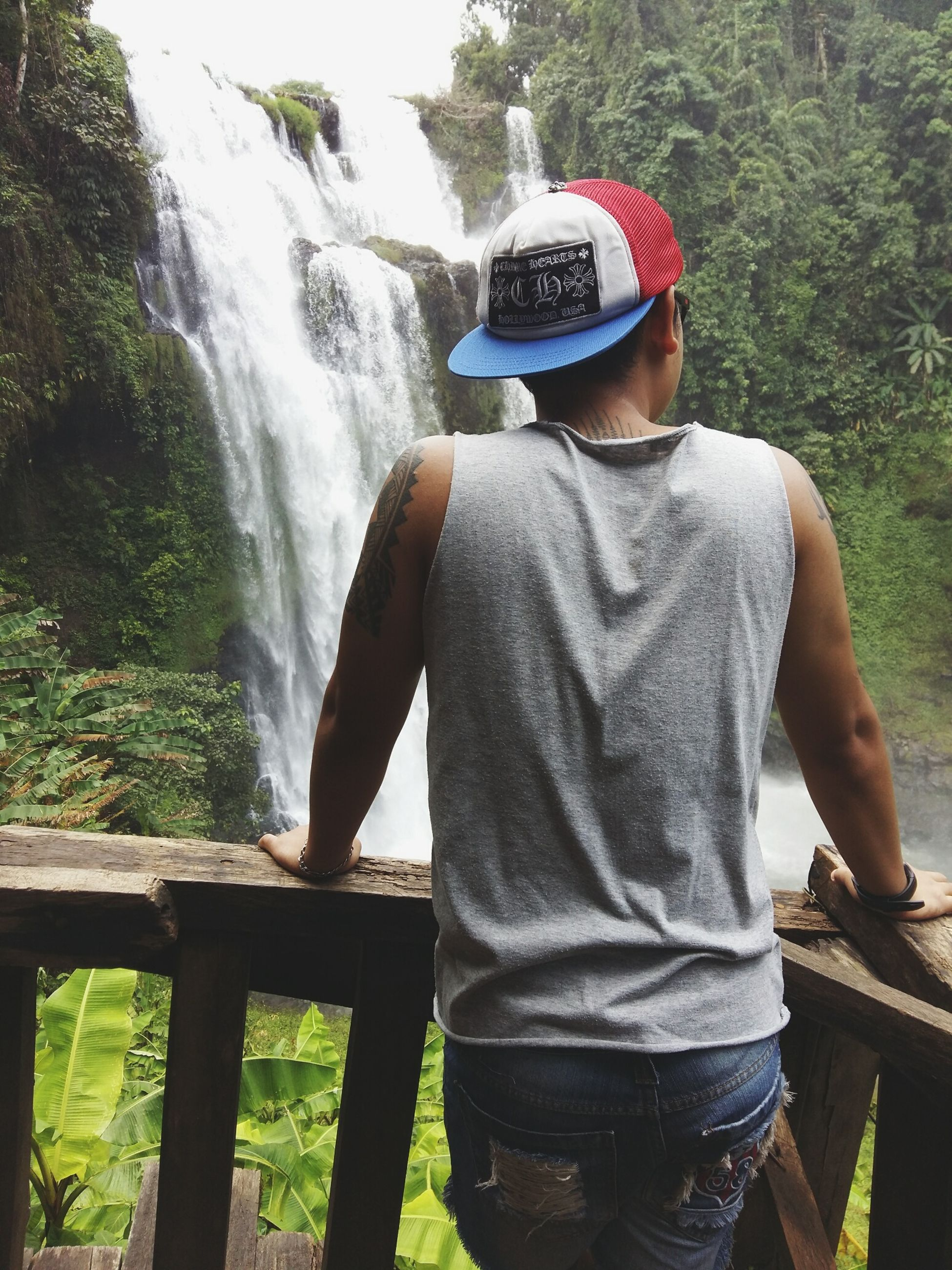 lifestyles, leisure activity, casual clothing, rear view, standing, water, waterfall, men, three quarter length, mountain, day, rock - object, nature, outdoors, flowing water, tree, motion, flowing