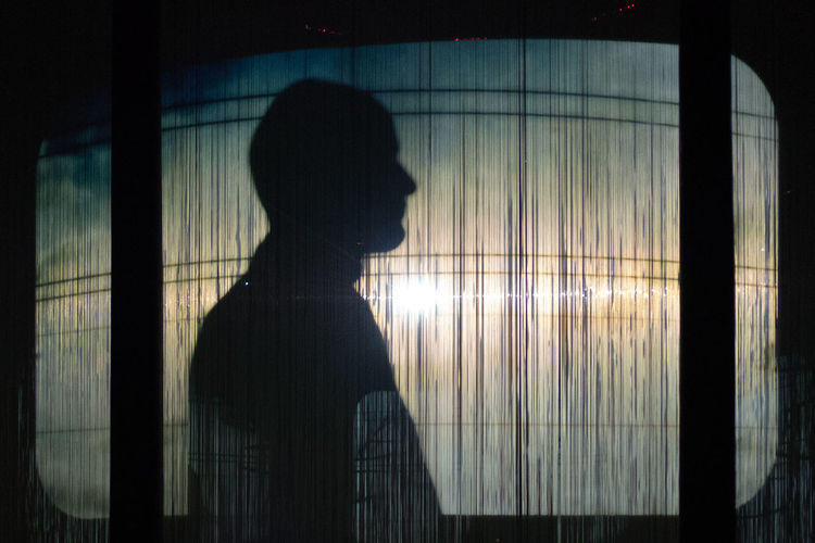 Silhouette of man standing against window