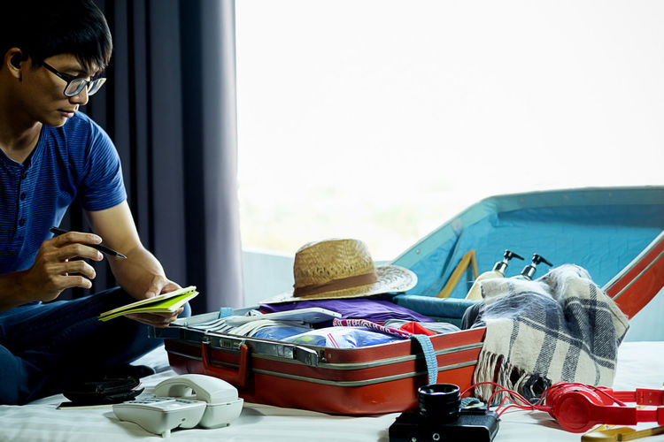 Boys Casual Clothing Child Childhood Day Indoors  Innocence Lifestyles Luggage Males  Men One Person Packing Preparation  Real People Sitting Suitcase Travel Window