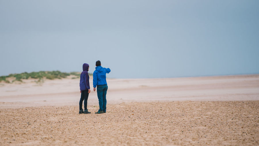 Rear view of couple on beach against clear sky
