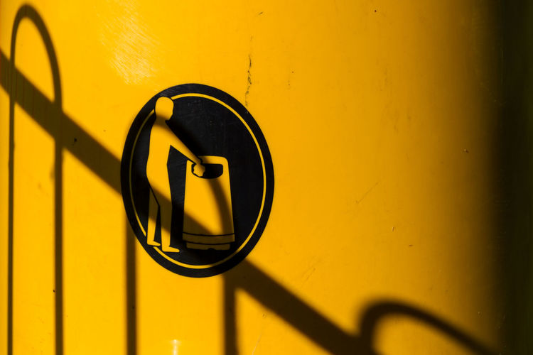 Close up of fence shadow on yellow litter bin with bin your litter logo
