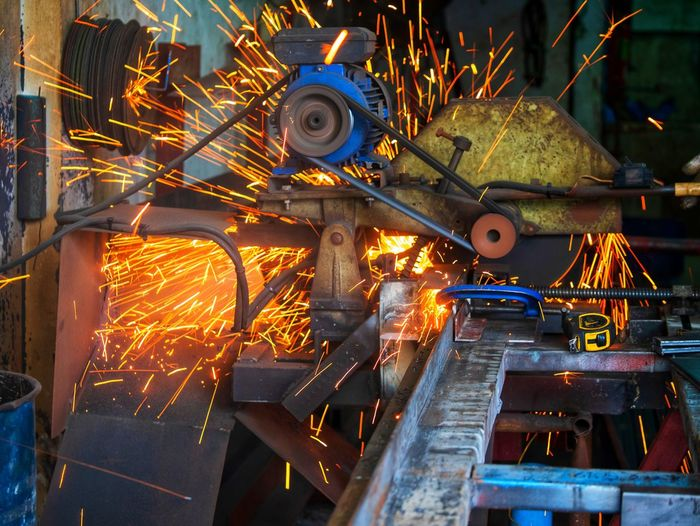 Low angle view of illuminated industry. worker grinding cutting metal sheet grinder machine welding