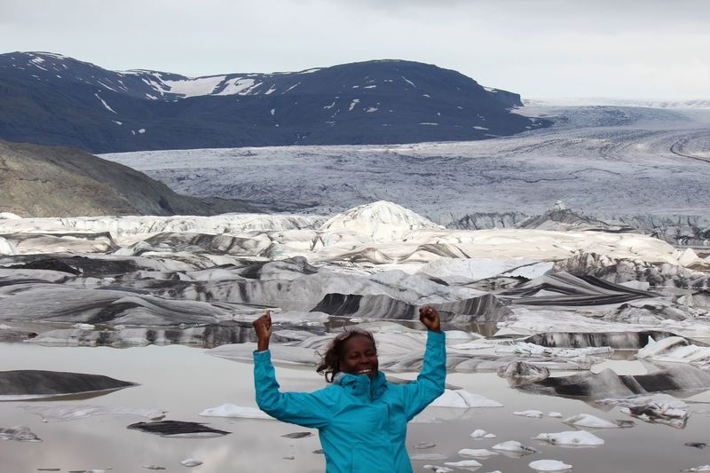 Mature woman with arms raised standing against glacier