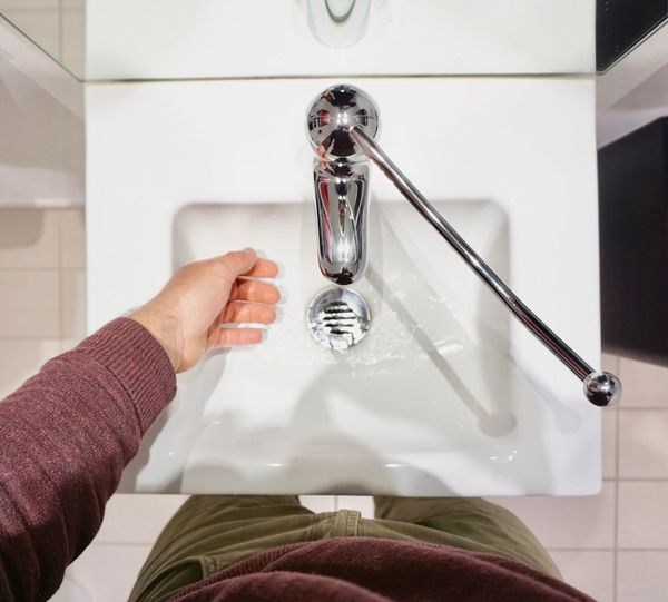 Close-up of woman hand holding faucet