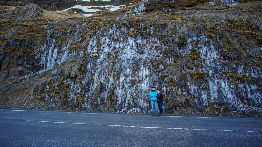 Portrait of couple standing by road against rock formation during winter