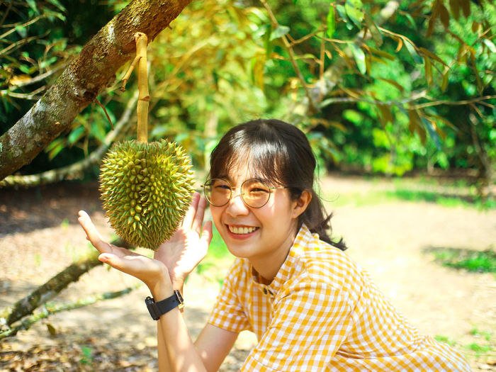 Portrait of smiling young woman showing fruit on tree