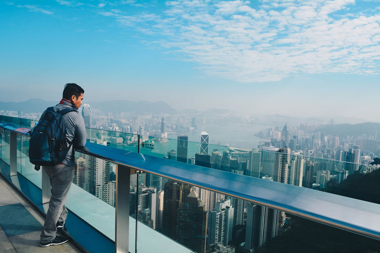 Man standing by railing against cityscape and sky