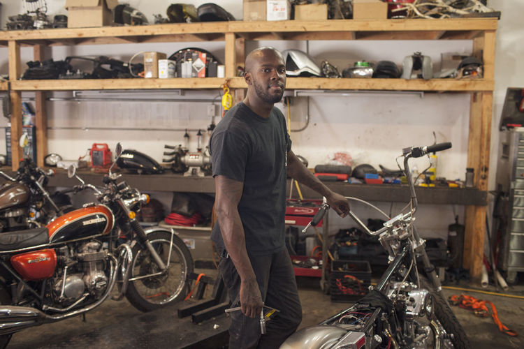 A young man in a garage with motorycles.