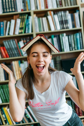 Close-up of smiling girl with book at library