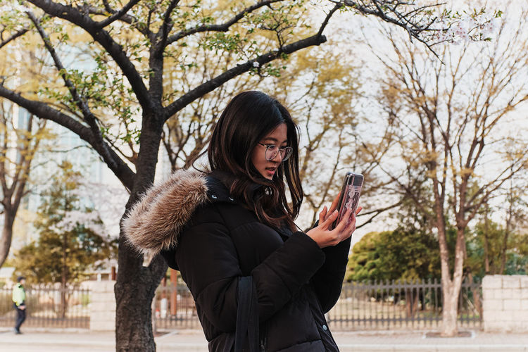 Young woman using phone while standing on tree