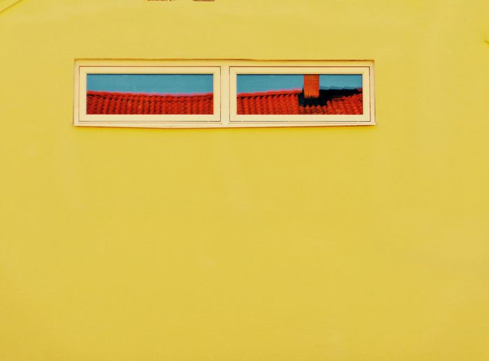 Low angle view of multi colored windows on yellow wall of building