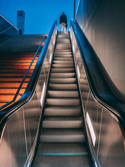 Low Angle View Of Man Standing On Escalator At Dusk