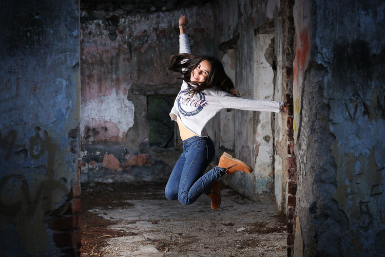 Portrait of young woman jumping at abandoned building