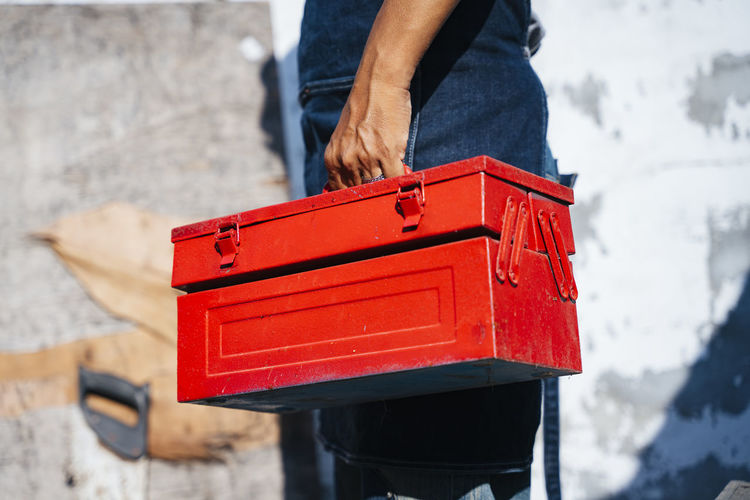 Low section of man holding red box standing outdoors