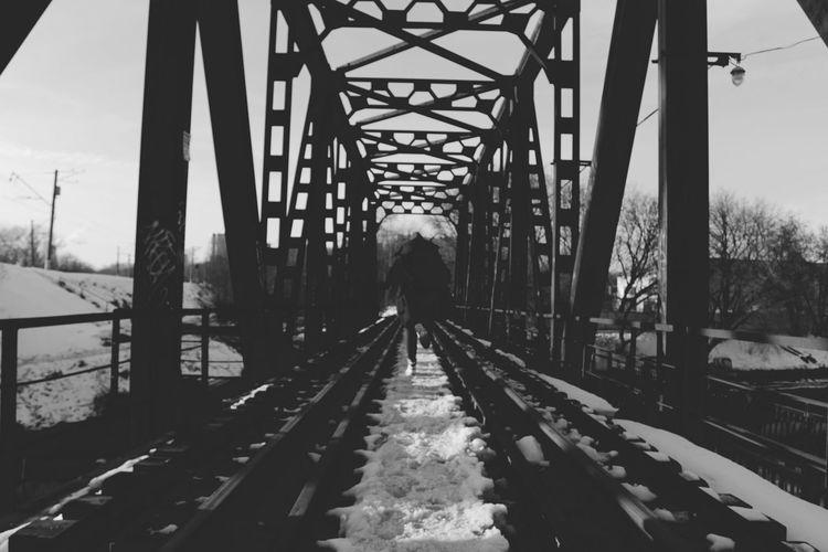 Rear view of man on bridge in winter