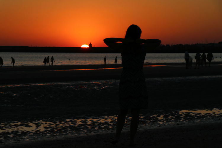 Woman posing against sunset Sunset Land Water Real People Beach Sky Silhouette Nature Sea Lifestyles Orange Color Men Standing Beauty In Nature People Leisure Activity Scenics - Nature Group Of People Incidental People Outdoors