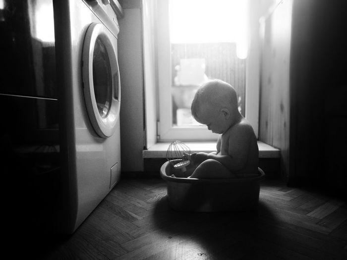 Cute boy sitting in tub at home