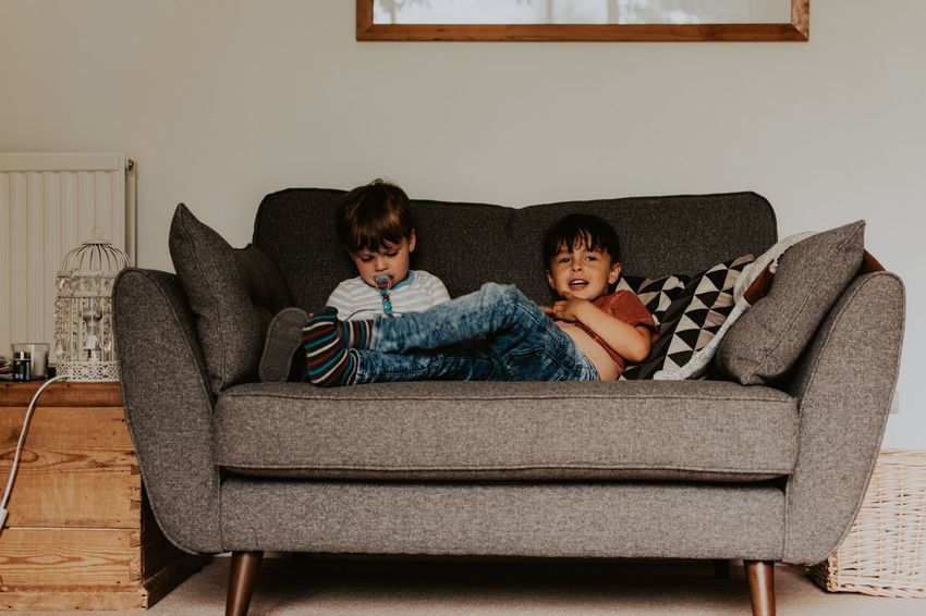 Film Sofa Boys Child Childhood Living Room Indoors  Males  Two People Children Only Domestic Life Sitting Sibling Togetherness Full Length Looking At Camera Relaxation Bonding Real People Lifestyles Pillow