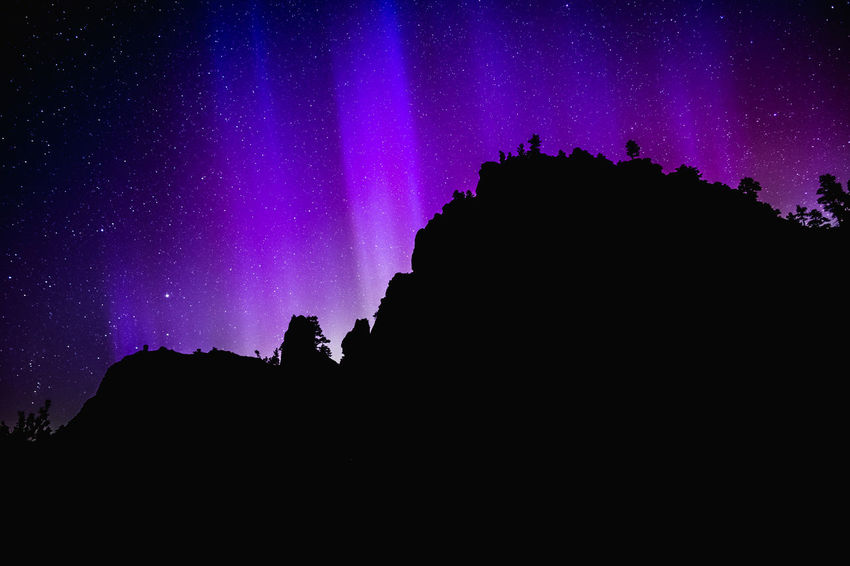 Aurora Borealis lights shine from behind a rock formation in Cascade, Montana, USA. Aurora Aurora Borealis Montana Perspectives On Nature Astronomy Auroraborealis Beauty In Nature Nature Night Outdoors Purple Scenics Silhouette Sky Star - Space
