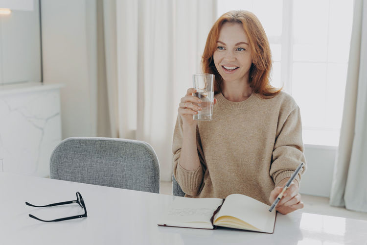 Portrait of a smiling young woman drinking glasses