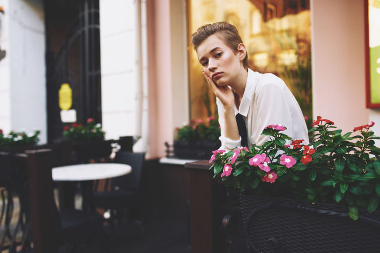 Woman sitting by building