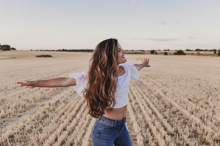 Carefree mid adult woman with arms outstretched standing on agricultural field