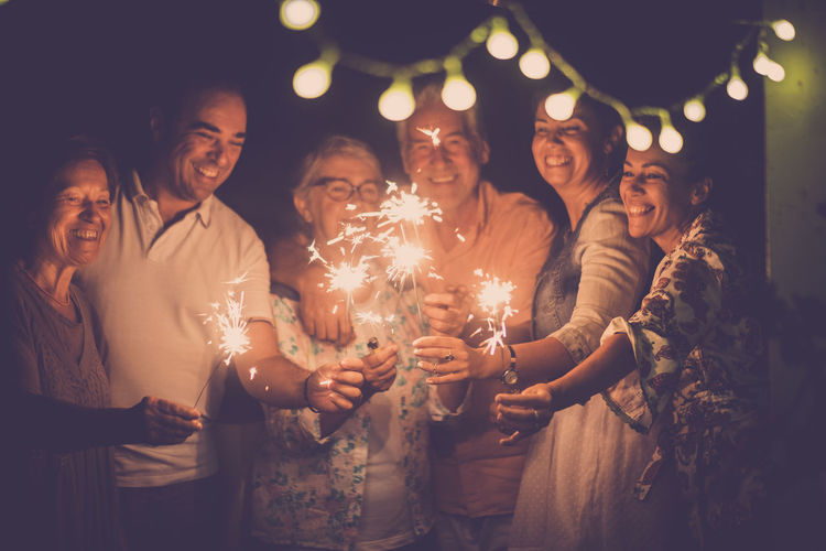 Happy Friends Holding Sparklers At Night