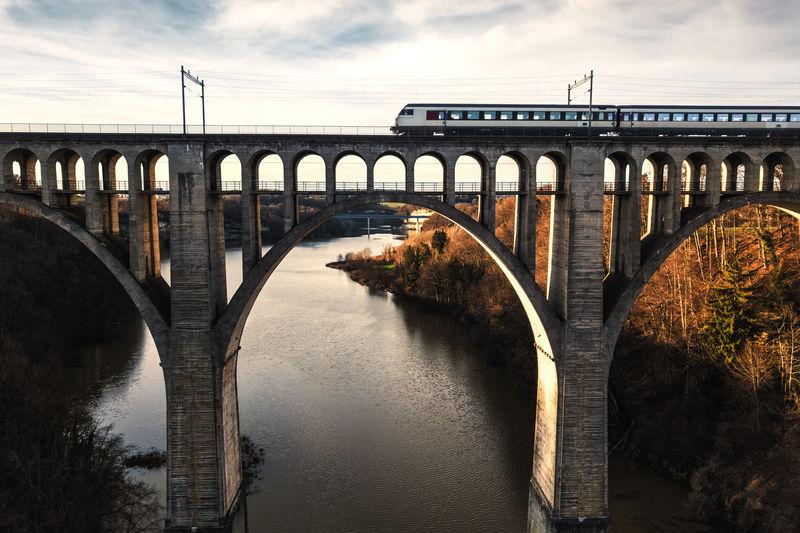Train on arch bridge over river against sky