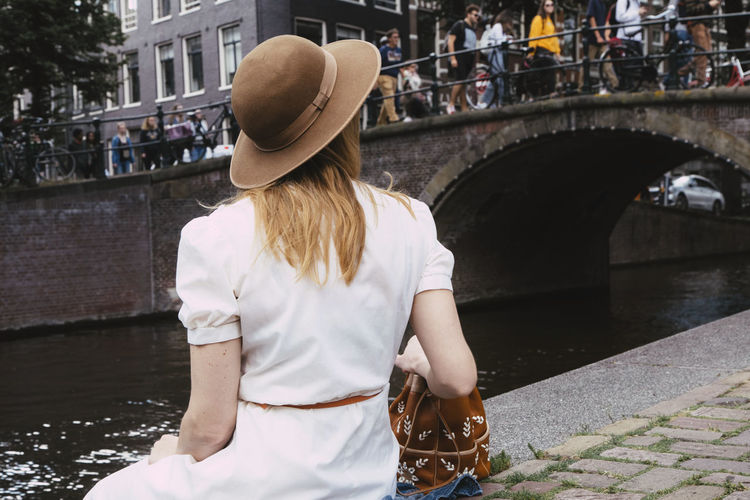 Rear view of woman with umbrella in canal