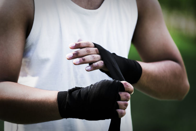 Midsection of boxer tying bandage while standing outdoors