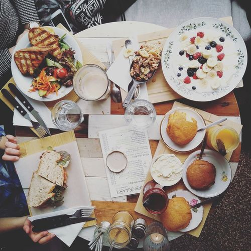 Midsection of friends having brunch served on table
