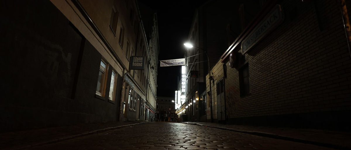 Narrow street amidst buildings at night