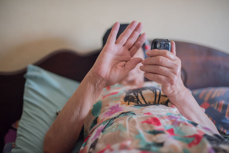 Woman using phone while showing stop sign on bed