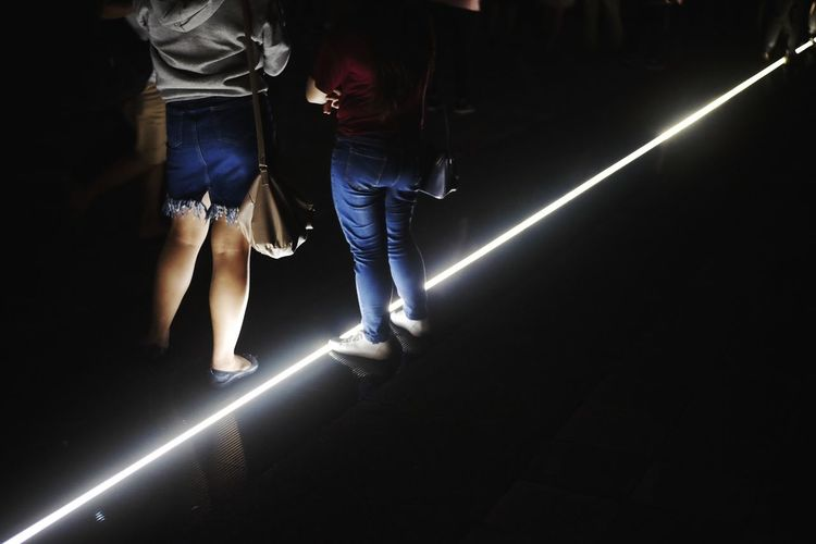 Low section of women standing on illuminated floor