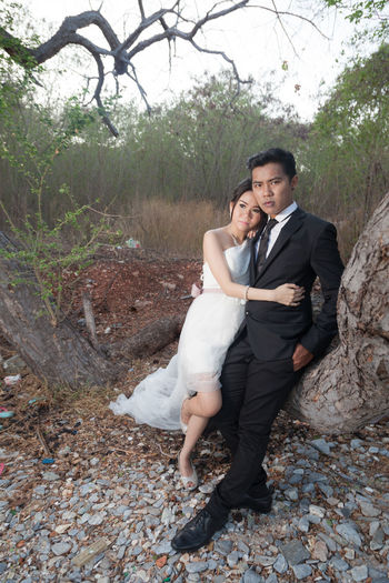 Bride And Groom Embracing By Tree In Forest