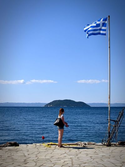Side view of woman standing by greek flag against sea