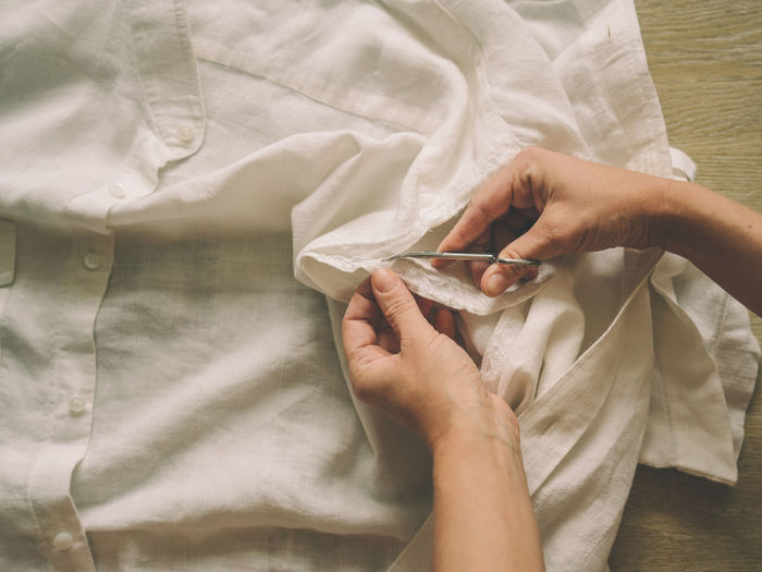 High angle view on woman cutting clothing with scissors