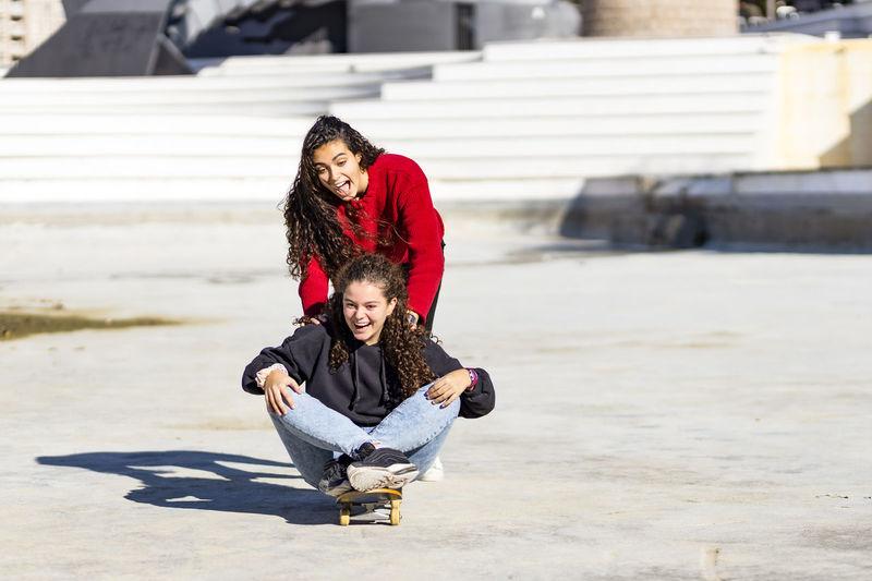 Playful female friends enjoying with skateboard outdoors