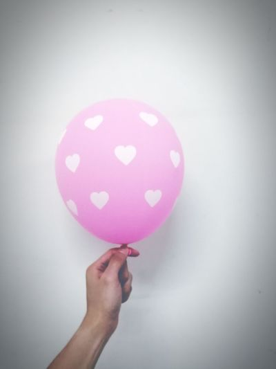 Close-up of hand holding pink balloons against white background