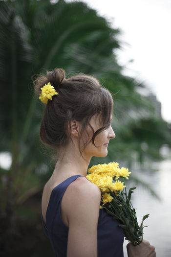 a flower in her hair Beauty In Nature Casual Clothing City Life Day Flower Focus On Foreground Freshness Leisure Activity Lifestyles Long Hair Mountain Nature Outdoors Person Profile Standing Thailand Vacations Weekend Activities Woman Yellow Young Adult Young Women