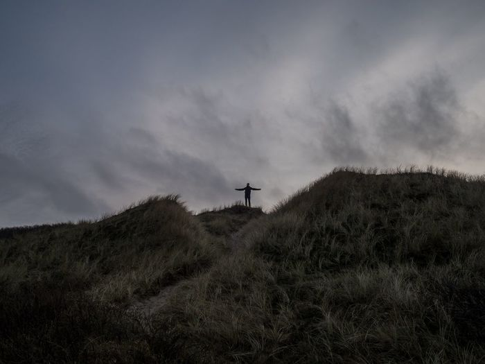 Low angle view of silhouette man standing on mountain against cloudy sky