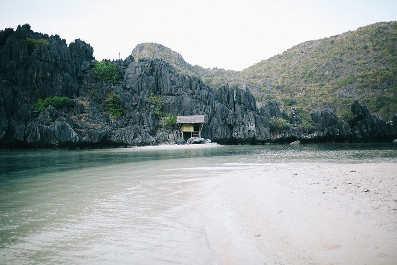 Deserted island with one hut in philippines Water Mountain Tranquility Sky Scenics - Nature Tranquil Scene Beauty In Nature Nature No People Land Architecture Sea Built Structure Waterfront Clear Sky Idyllic Rock Environment Outdoors Island Hut Huts Philippines Rocks Mountain Range