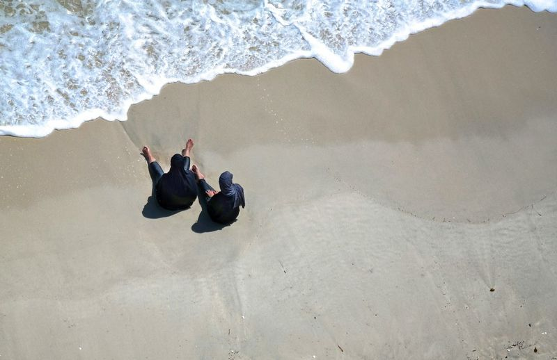 High Angle View Of Carefree Women Sitting On Shore At Beach