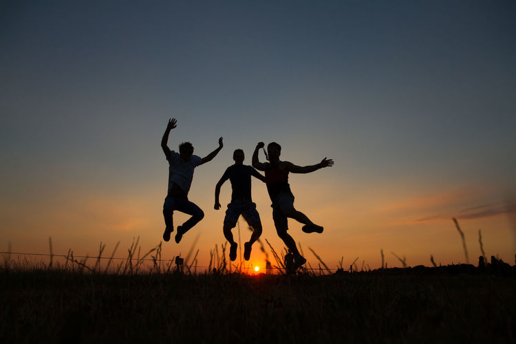 Silhouette Of Three Men Jumping On Field