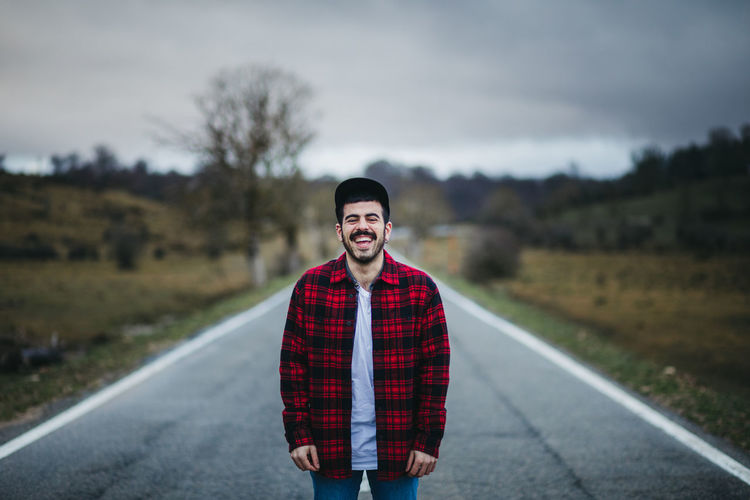 Portrait of a smiling young man standing on road