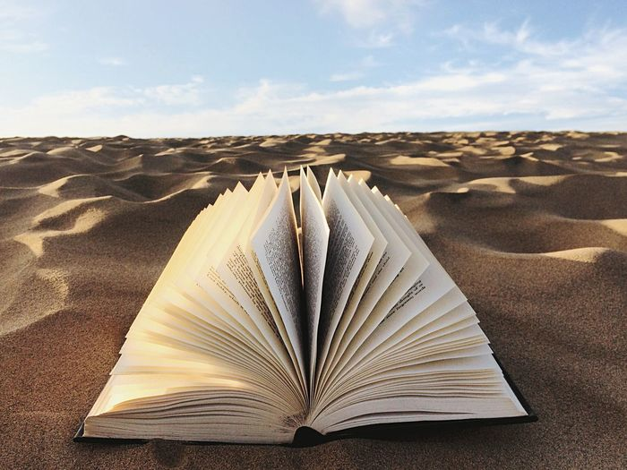 Close-up of open book on sand