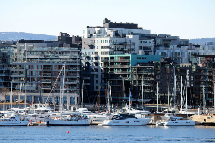 Sailboats Moored In Sea Against Buildings In City